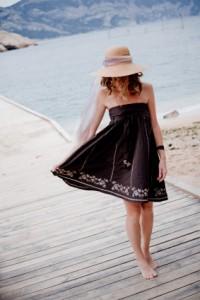 Frau mit schwarzem Bandeau Kleid am Meer